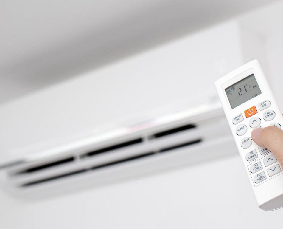 Close up of a Female Hand operating a Remote control of a Domestic Air conditioner unit of a modern house